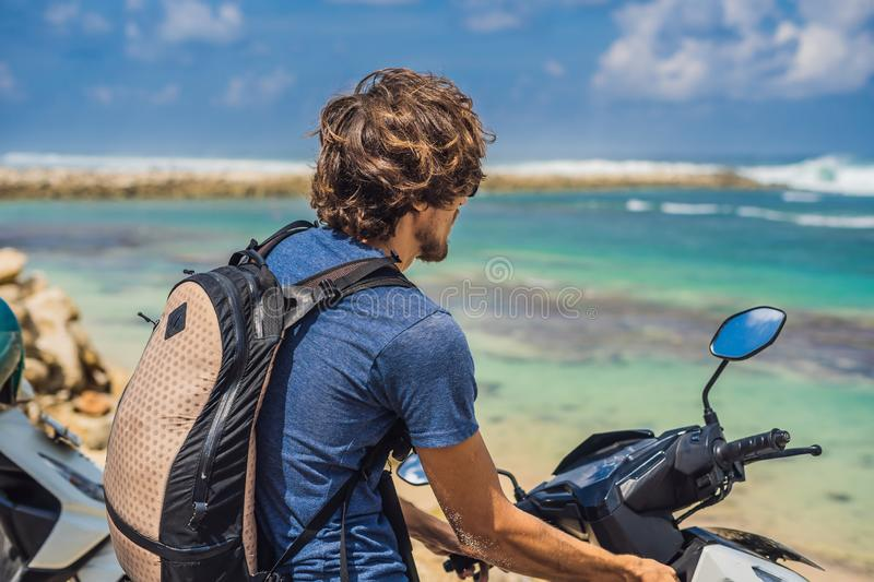 A man on a moped, motorbike admires the beautiful sea royalty free stock photos
