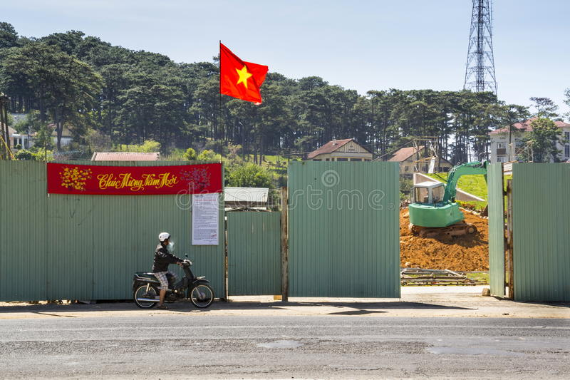 Man on motorbike in front of construction site with excavator and Vietnamese flag on February 10, 2012 in Dalat, Vietnam. royalty free stock photography