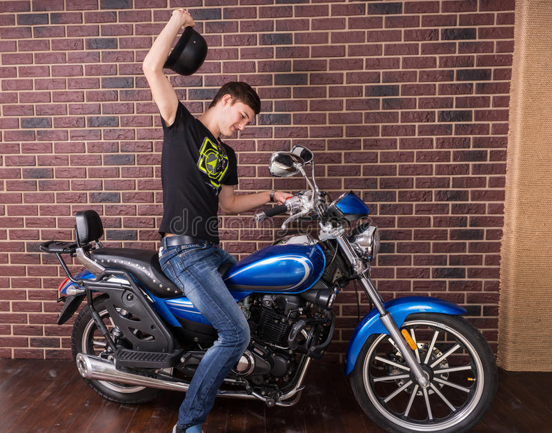 Man on a Motorbike Raising his Black Helmet. Young Man Sitting on his Sports Motorbike While Raising his Black Helmet on a Brick Wall Background royalty free stock photo