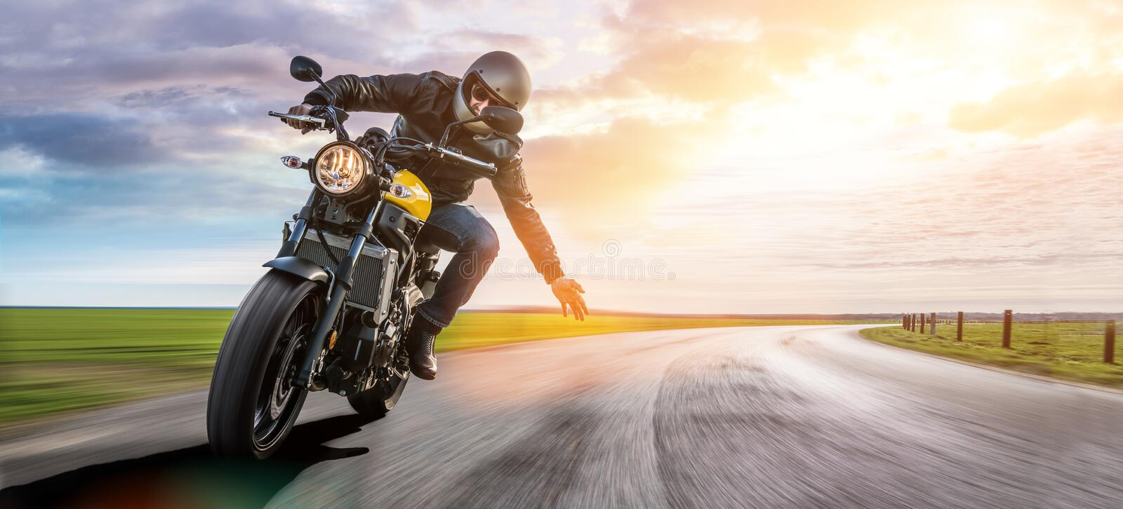 Man on a motorbike on the road riding. having fun driving the empty road on a motorcycle tour journey. royalty free stock photo
