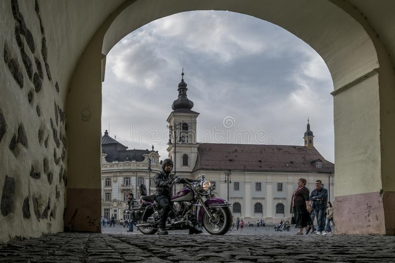 A man on a motorbike standing in front of the big square in Sibiu, Romania. royalty free stock photos