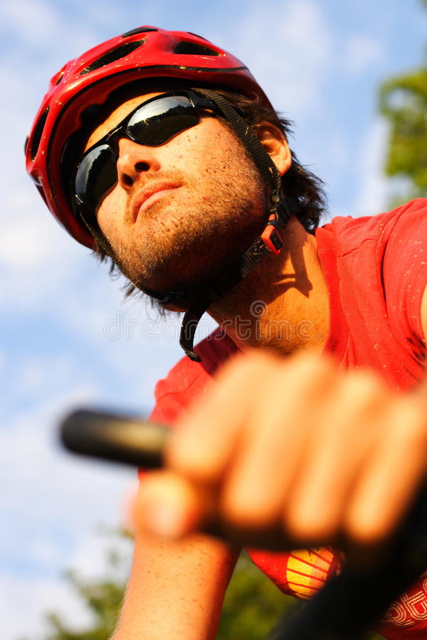 Man on mountain bike. Closeup of young man riding a mountain bike in the forest on a sunny day royalty free stock image