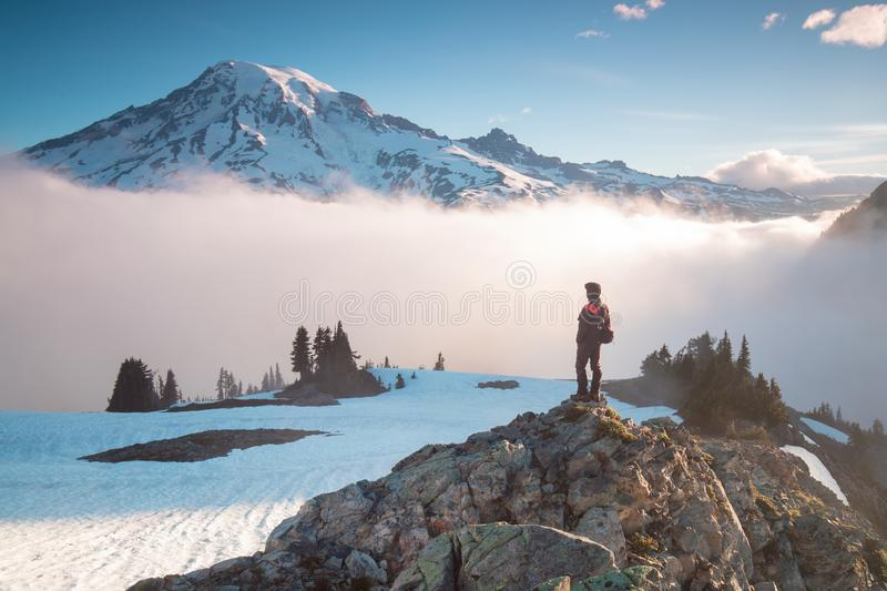 Man on the mountain peak looking on mountain valley with low clouds at colorful sunrise in autumn in Mount Rainier National park. royalty free stock photography
