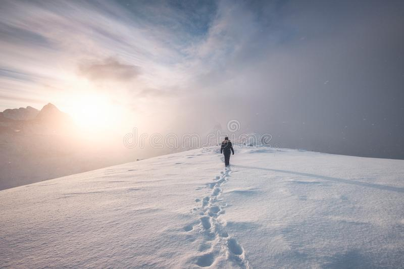 Man mountaineer walking with snow footprint on peak ridge. In winter stock photography