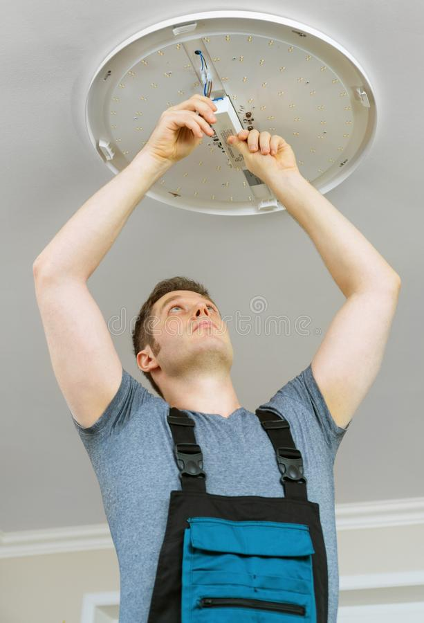 Man mounting LED lamp stock images