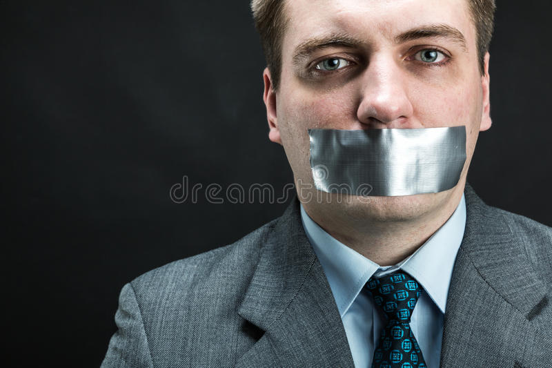 Man with mouth covered by masking tape. Preventing speech, studio shoot royalty free stock photo