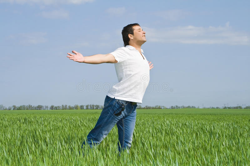 Man moves in a green field of grass