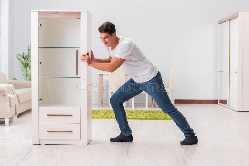 The man moving furniture at home. Man moving furniture at home stock photos