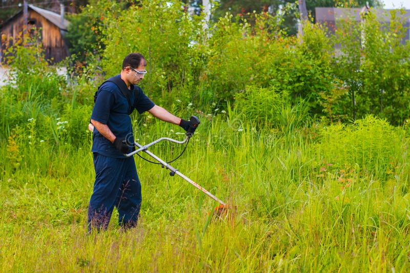 Man mowing grass with a lawn mower. Man with a manual lawn mower mows the grass royalty free stock photos