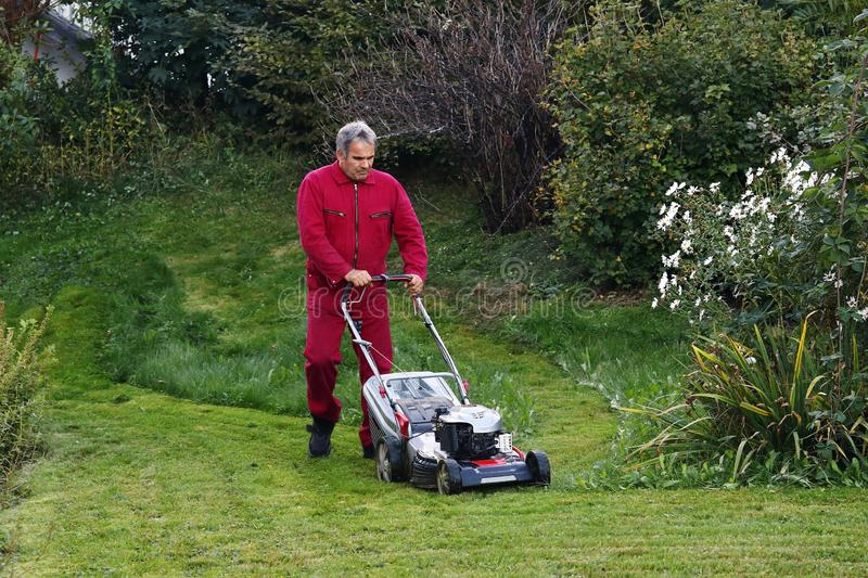 A man mowing the lawn stock photos