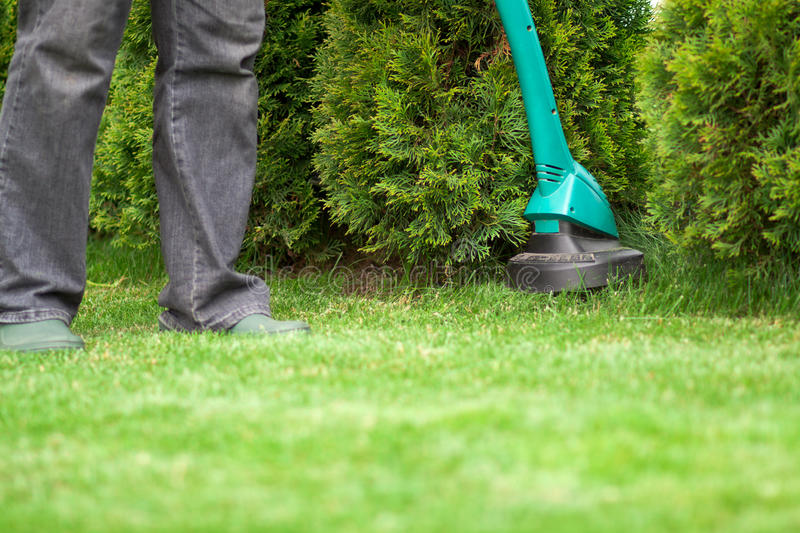 Man mowing lawn grass trimmer royalty free stock photos