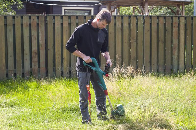 Man mowing the overgrown lawn. Man with electric lawn mower . Country life. stock images