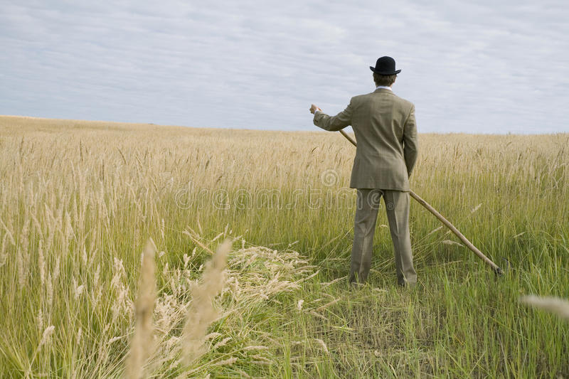 A man mows a grass with a scythe royalty free stock photography
