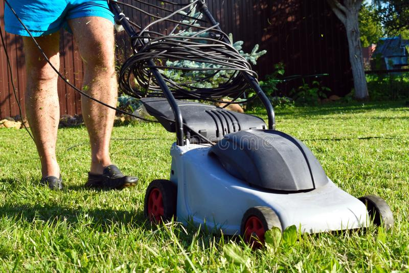Man mows green lawn in garden in summer royalty free stock image