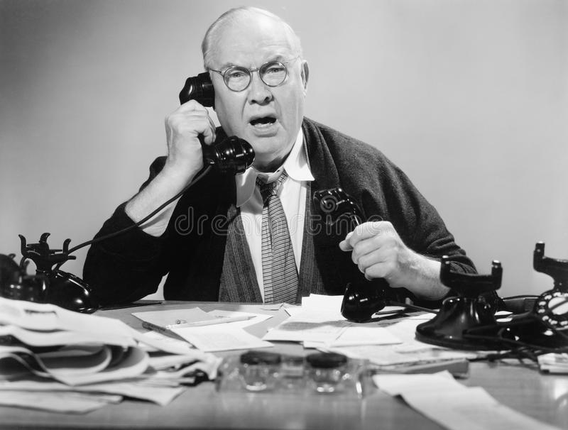 Man on multiple telephones looking angry. (All persons depicted are no longer living and no estate exists. Supplier grants that there will be no model release royalty free stock image