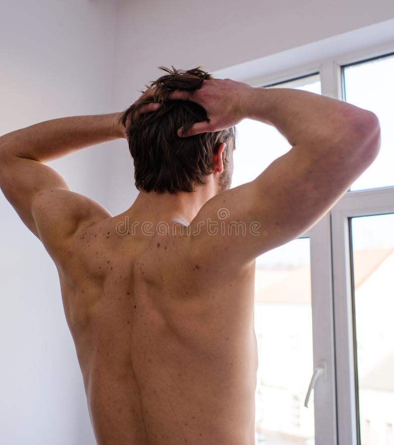Man muscular back stretching hands rear view. Get ready to new day. Morning stretching daily exercise for healthy back stock photo
