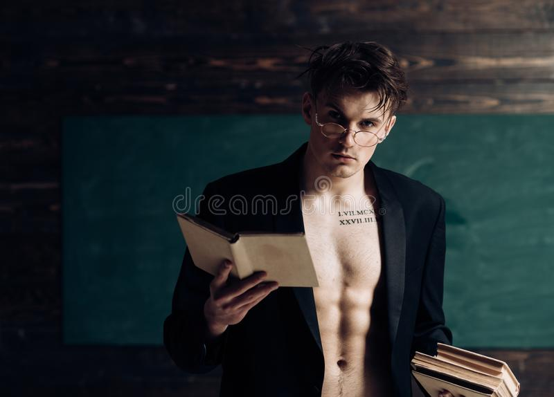 Man with muscular torso, six packs, wears classic jacket and eyeglasses, looks attractive, chalkboard on background stock photography