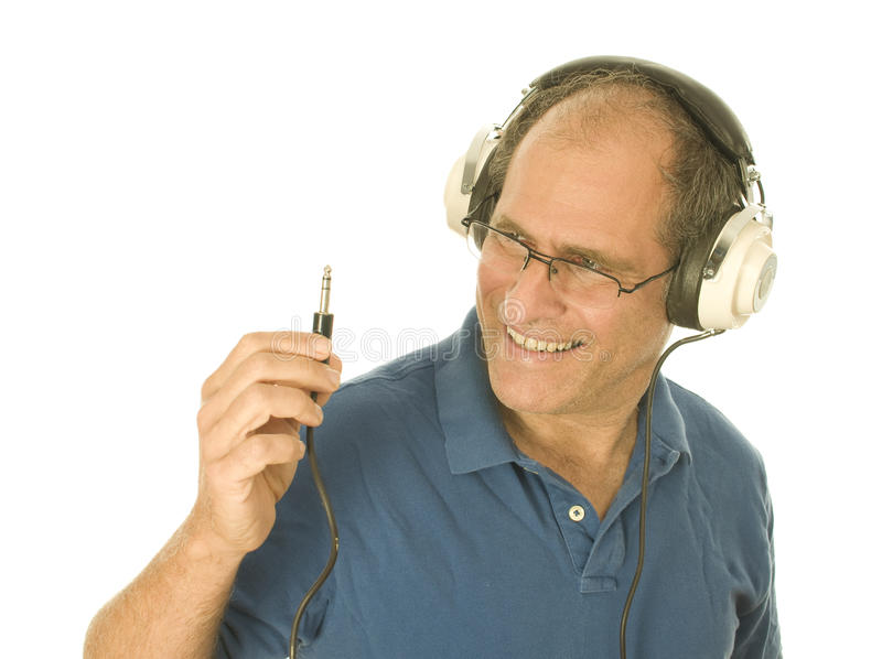 Man music head phones looking at plug stock images