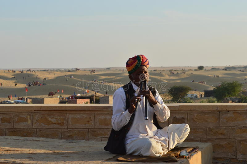 Man with musical instrument in desert stock image
