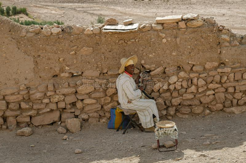 Man musician playing laud at the Kasbah Ait Ben Haddou in Ouarzazate, Morocco October 2019. Hadu, fortified, city, ksar, draa-tafilalet, africa, moroccan stock photography