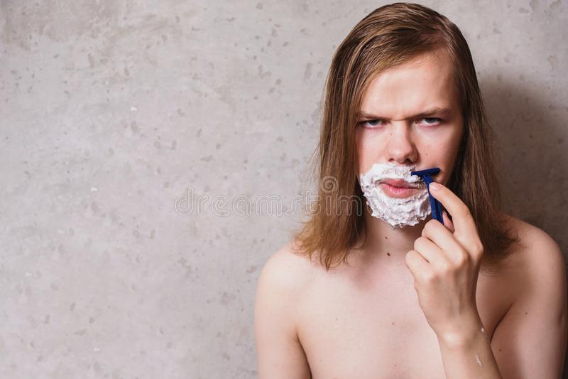 A man with a mustache and a beard with long wet hair on the background of gray walls. A man with razor and shaving foam on his face shaves his beard royalty free stock images