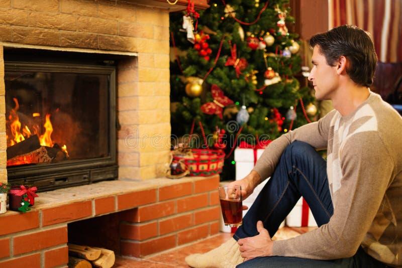 Man nära spisen i jul dekorerat hus arkivbild
