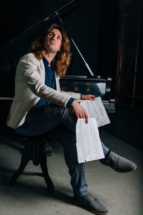 Man nära svarta blickanmärkningar för ett piano arkivfoto