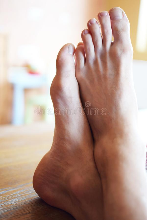 Man bare feet on wooden table royalty free stock photo
