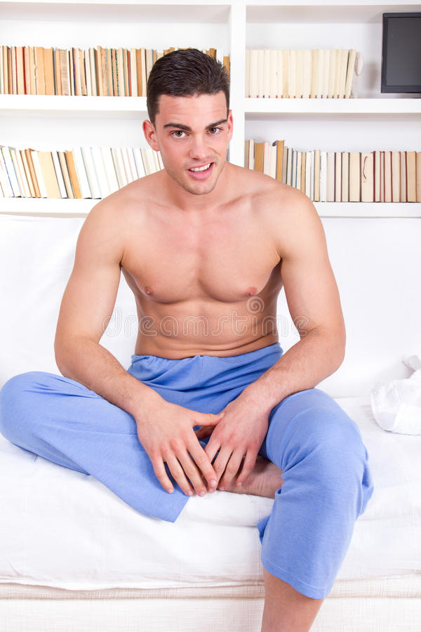 Man with naked torso in pajamas relaxing on sofa stock photos