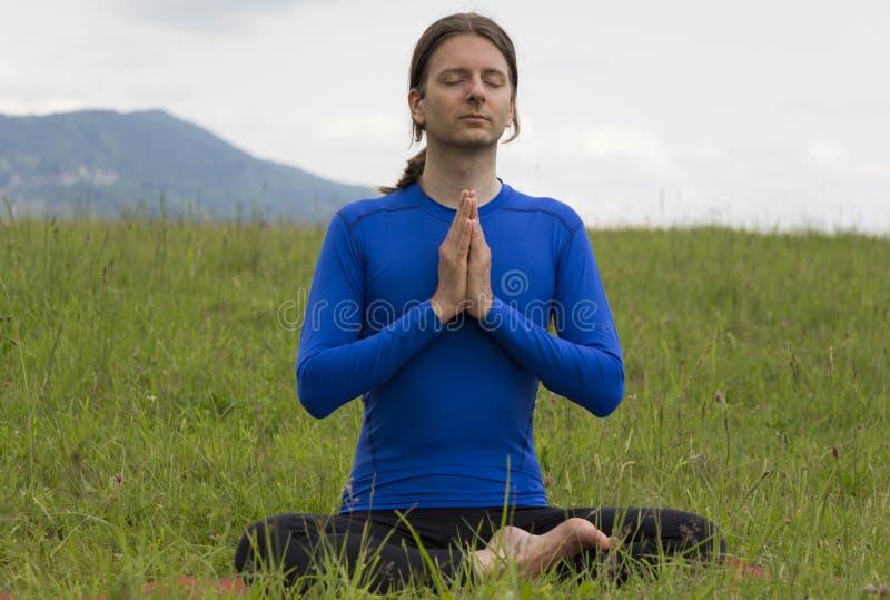 Man in Namaste pose outdoors royalty free stock image