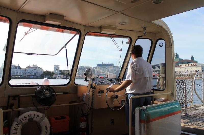 Man navigating ferry at Disney. Captain navigating ferry boat across a lake at Disney in Orlando, Florida stock photo