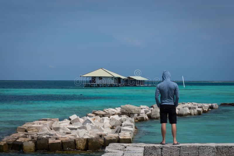 A man with navy jacket and short pants standing and looking to floating house and scattered stones with beautiful turquoise ocean stock photography