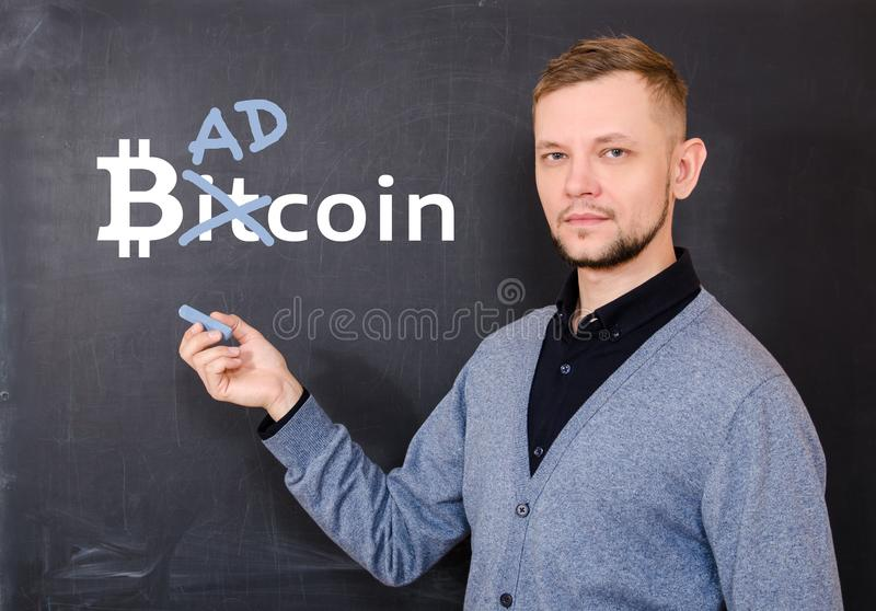 Man near a black school board on which is written bitkoin, part of the word Bitcoin is replaced by Bad stock photo