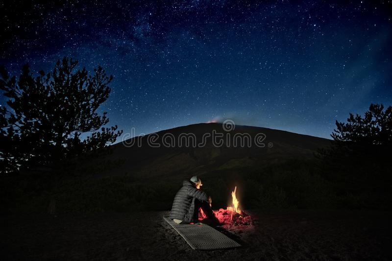Man Near Campfire Under Etna Volcano And Starry Sky, Sicily. Alone man resting by the campfire under Etna Volcano and starry sky, Sicily stock images