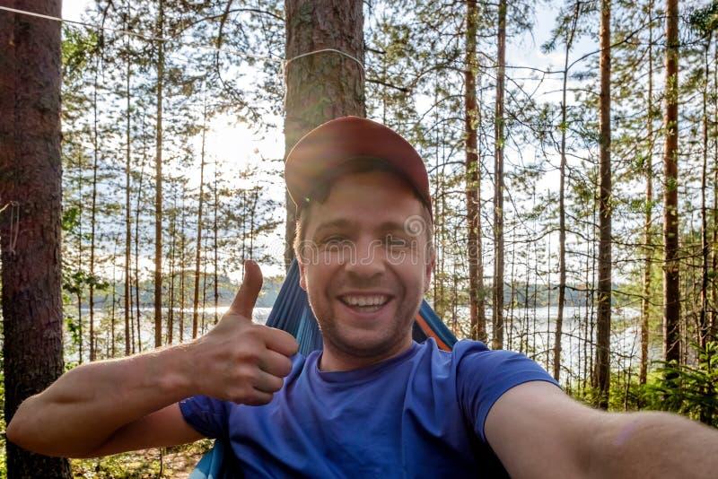 Man near lake hanging on hammock showing thumb up takes selfie stock photography