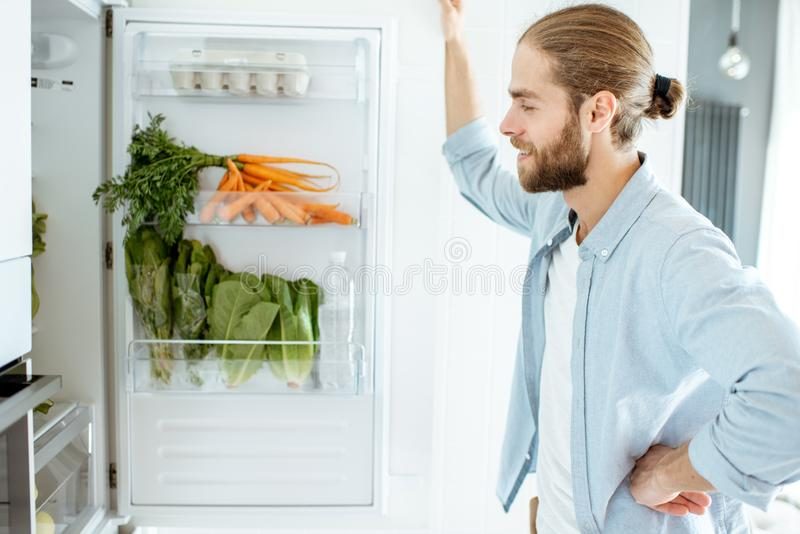 Man near the refrigerator full of healthy food at home royalty free stock photo