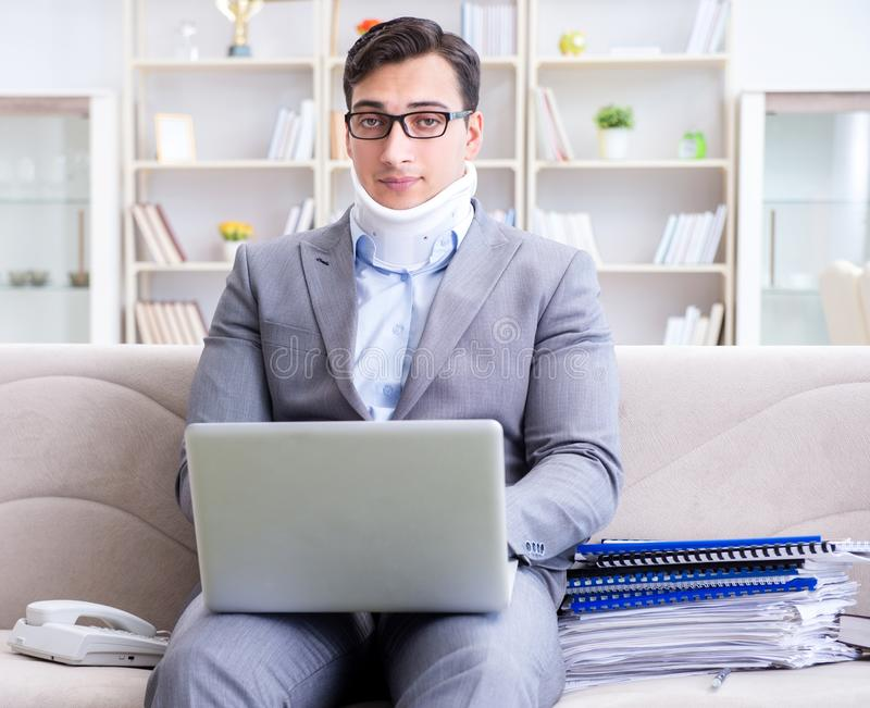 Man in neck brace cervical collar working from home teleworking stock photo