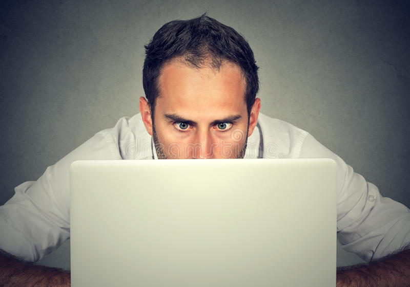 Man nederlaget bak en bärbar dator som stirrar på skärmen med ett chockat framsidauttryck royaltyfri foto