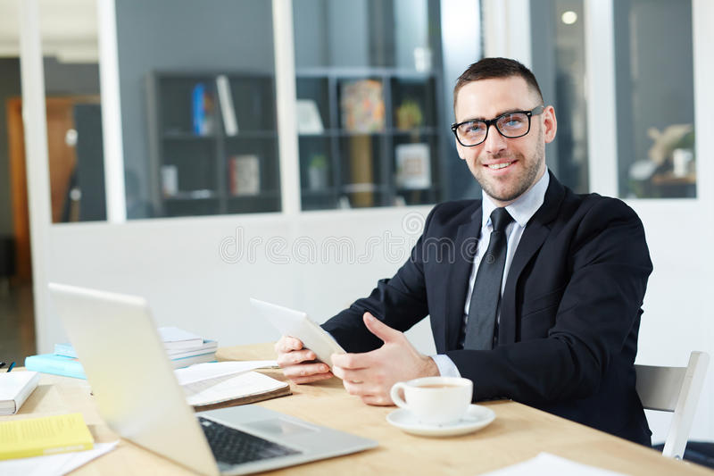 Man networking. Happy young economist with gadget sitting by his workplace royalty free stock image