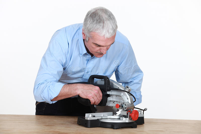 Man with new mitre saw. Man figuring out how to operate his new mitre saw stock photos