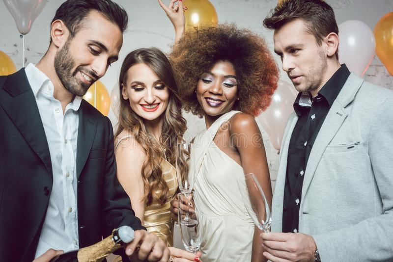 Man, on new year or birthday party opening bottle of champagne stock photo