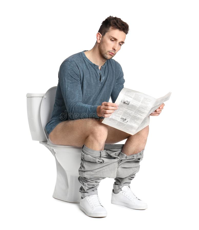 Man with newspaper sitting on toilet bowl royalty free stock images