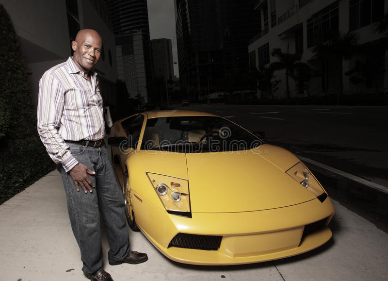 Man next to an exotic sports car. African American male next to an exotic sports car stock photography