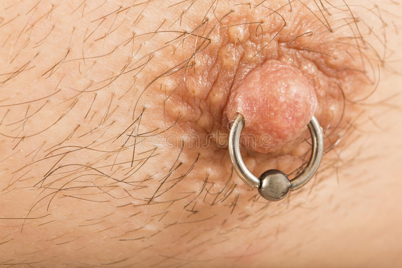 Man with nipple piercing. Close up of muscular male torso with a nipple piercing royalty free stock photo
