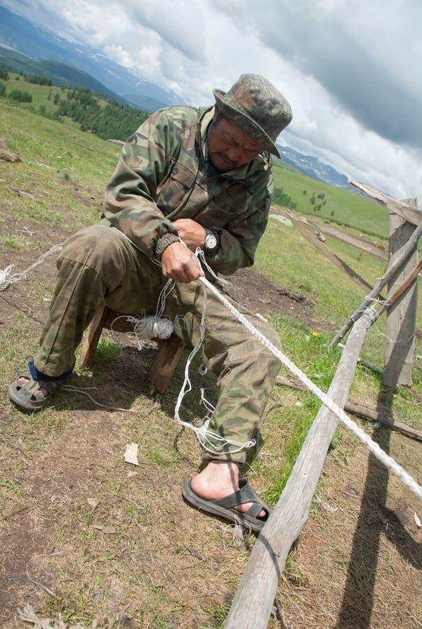 Man nomad weaving rope stock photo