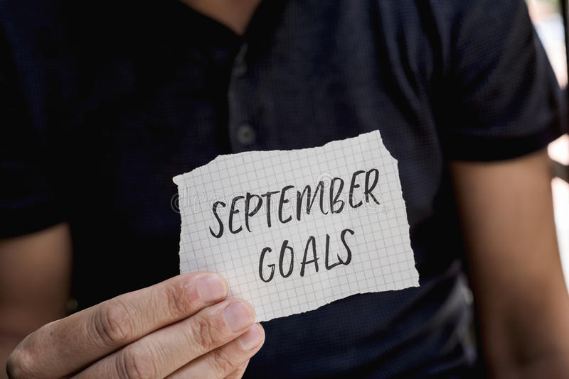 Man with a note with the text september goals royalty free stock image