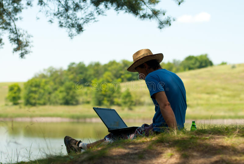 Man with notebook on riverbank royalty free stock images