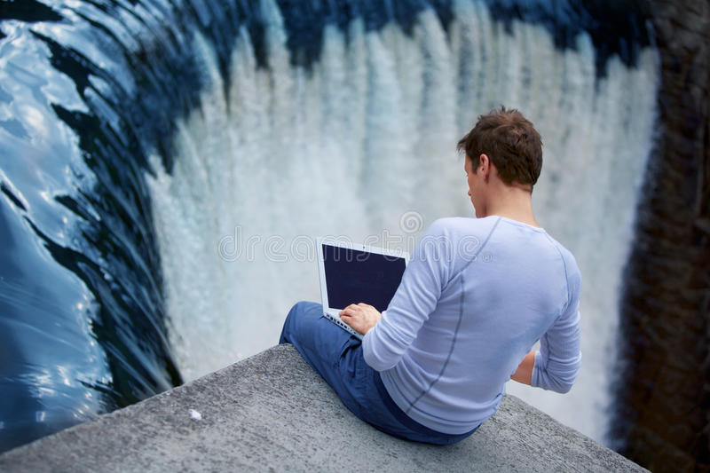 Man + notebook sitting over the waterfall. Man with notebook sitting at the bank of river over the waterfall
