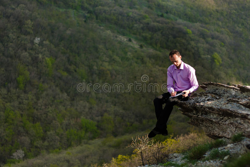 Download Man with notepad on stone stock photo. Image of life - 24783454