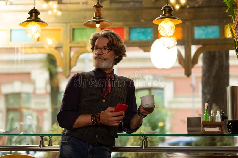 Man noticing one of his friends in the cafe. Looking closely. Handsome bearded man standing near the cafe table with a smartphone and a cup of coffee in his royalty free stock photos